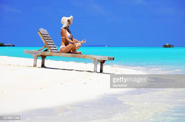 Woman in lotus pose on deck chair at the beach.