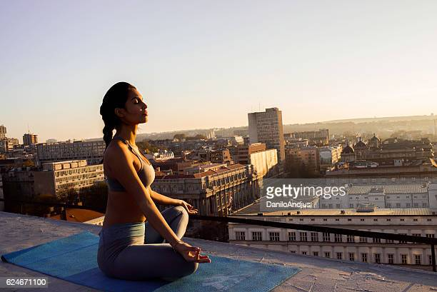 woman in lotus position meditating on the rooftop