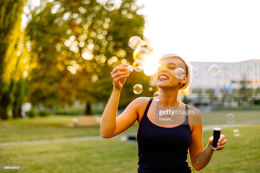 Woman in love, blowing bubbles in summer sunset