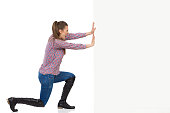 Young woman in jeans, black boots and lumberjack shirt pushing a white wall and shouting. Side view, full length studio shot isolated on white.