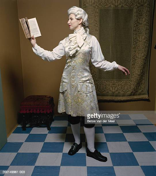 Woman in male costume from Regency era, holding book
