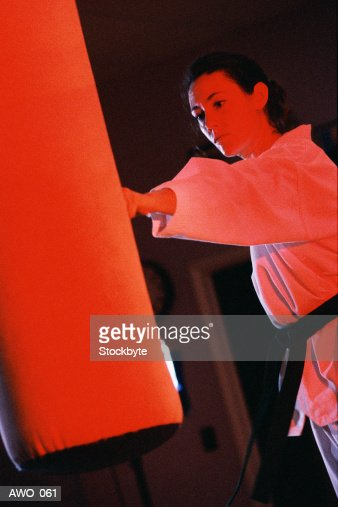 Woman in martial arts outfit punching bag, red lighting : Stock Photo