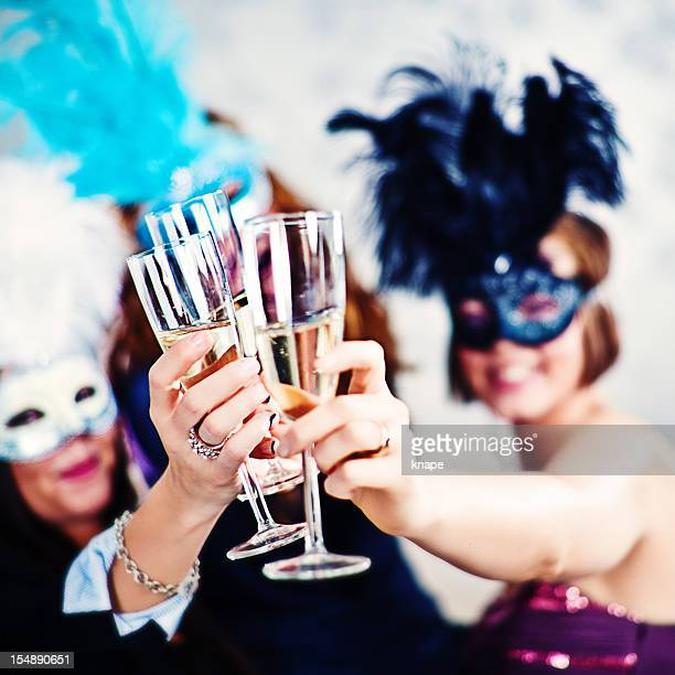 Woman in masks and drinking champagne