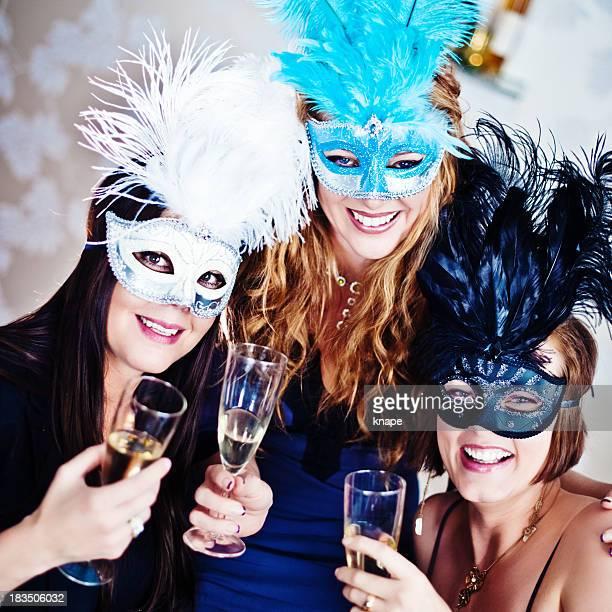 Mujer bebiendo champán en máscaras y