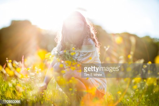 Woman in meadow at sunset : Stock Photo