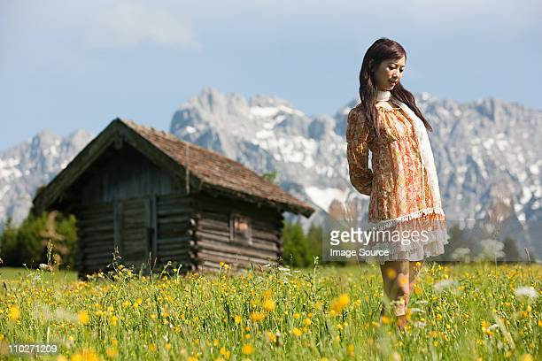Woman in meadow with Bavarian Alps in background, Germany