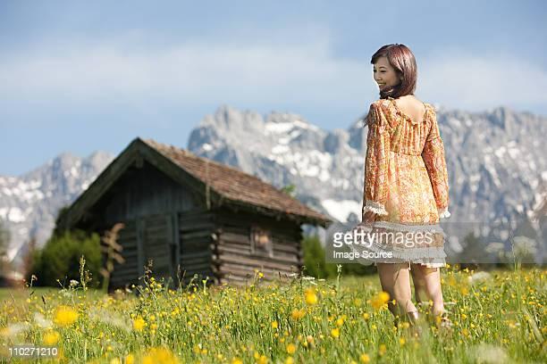 Frau in Wiese mit bayerischen Alpen im Hintergrund, Deutschland