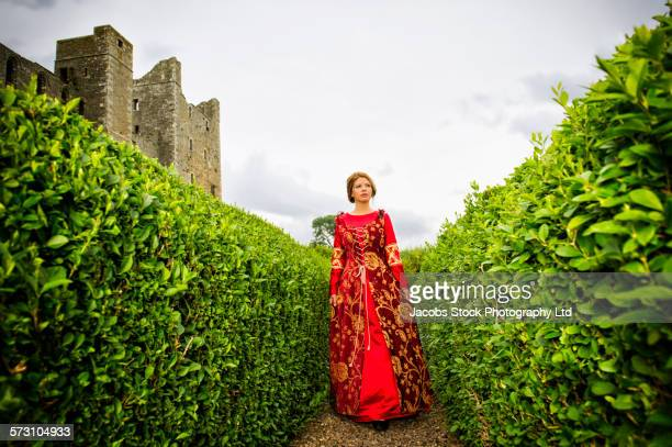Woman in medieval costume walking in hedge maze