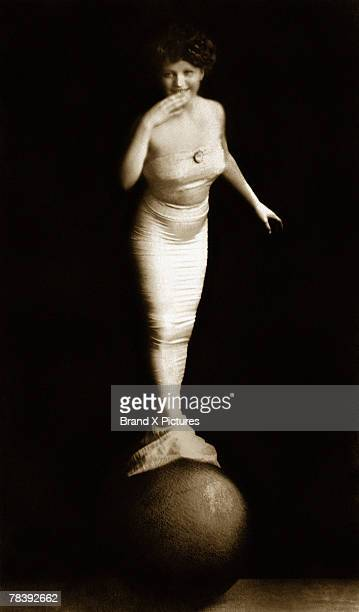 Woman in mermaid costume balancing on ball