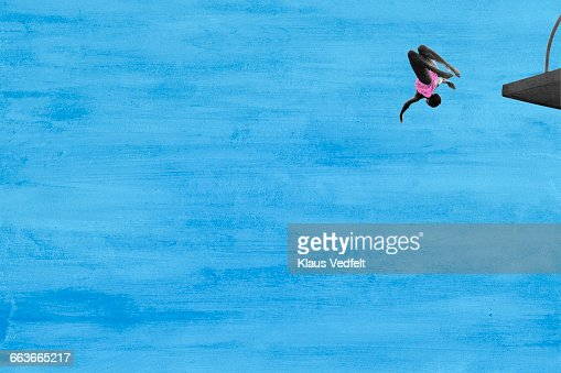 Woman in mid air diving from platform