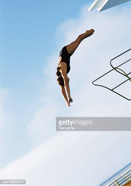 Woman in mid-dive, low angle view, full length, blue sky in background.