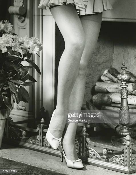 Woman in mini skirt standing by fireplace, (B&W), (Low section)