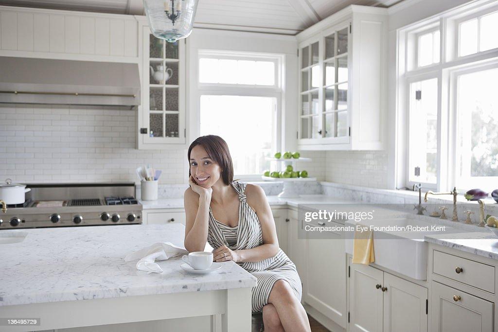 Woman in modern kitchen, portrait, smiling : Stock Photo