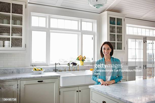 Woman in modern kitchen, portrait, smiling