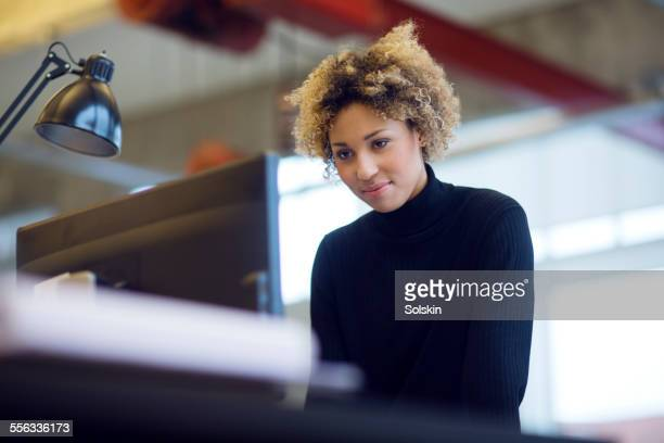 Woman in modern office, standing behind computer
