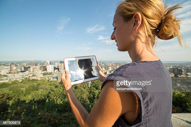 Woman in Montreal-Canada taking picture of cityscape using digital tablet
