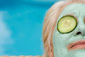 Woman in mud mask with cucumbers