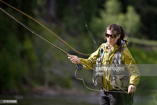 Woman in nature fly fishing for trout wearing sunglasses