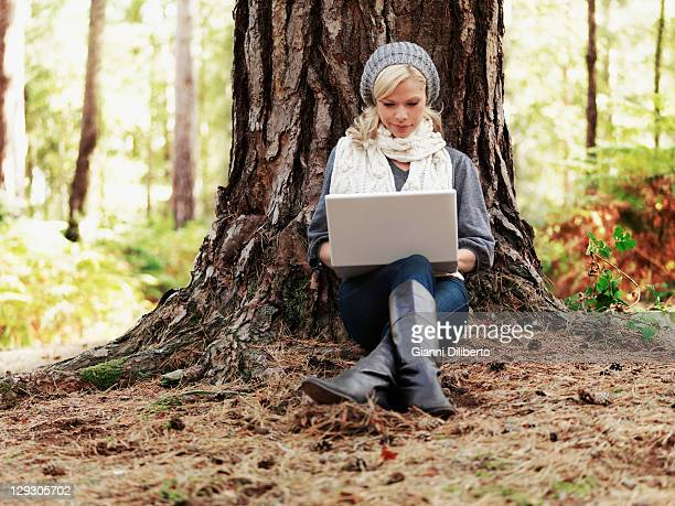 A woman in nature leaning against a tree and using a laptop