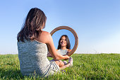 Dutch woman sitting on grass looking at  her mirror image. Wooden mirror on  woman's knee with reflection of herself. The european woman is sitting in the green meadow in a natural rural landscape. I