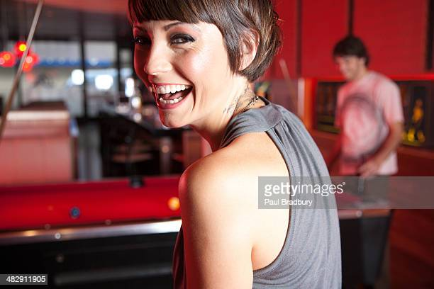 Woman in nightclub standing by pool tables smiling