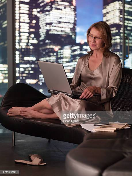 Woman in nightgown using laptop at night