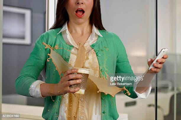 Woman in office environment spilling coffee