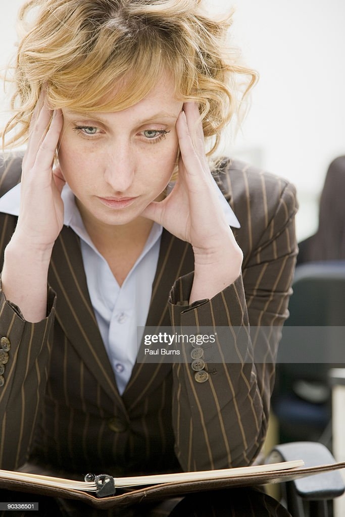 Woman in Office Looking Down : Stock Photo