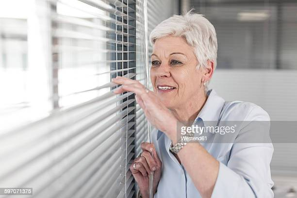Woman in office looking through blinds
