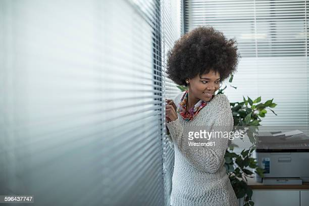 Woman in office standing at the window