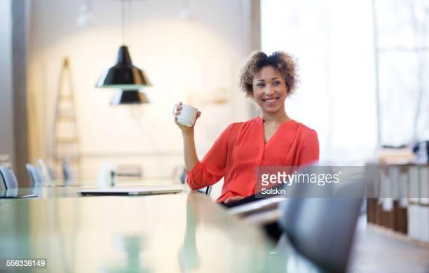 Woman in office taking a break, drinking coffee