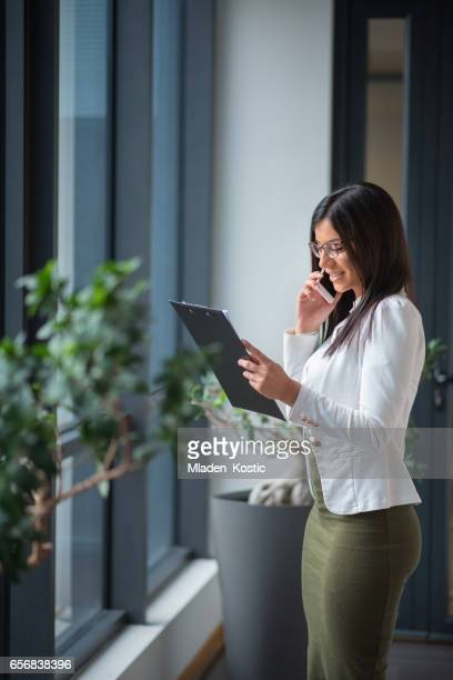 Woman in office talking on mobile phone and checking documents