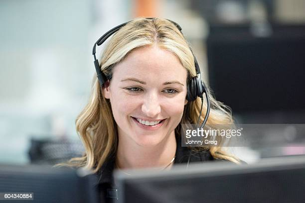 Woman in office wearing telephone headset, looking down