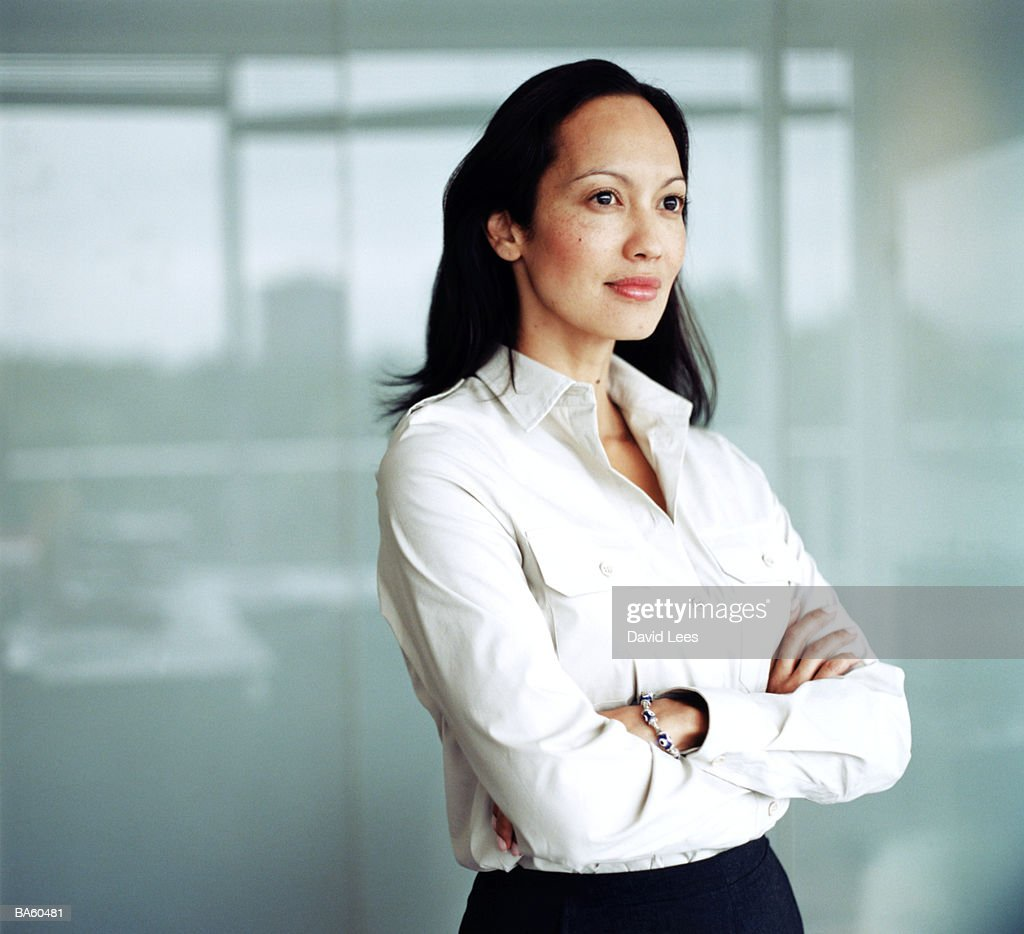 Woman in office with arms folded, close-up : Stock Photo