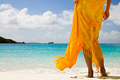 unrecognizable woman wrapped in orange sarong standing on a beach in the Caribbean