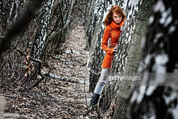 Woman in orange sweater is hiding at the woods