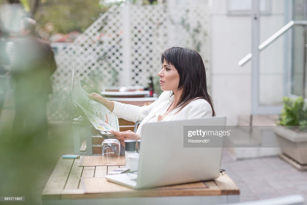 Woman in outdoor cafe with newspaper and laptop
