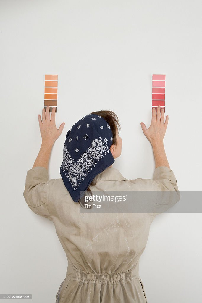 Woman in overalls comparing color samples against wall, rear view : Stock Photo