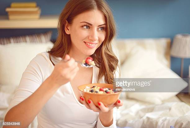 Femme en lingerie dans la chambre à coucher à manger muesli avec baies