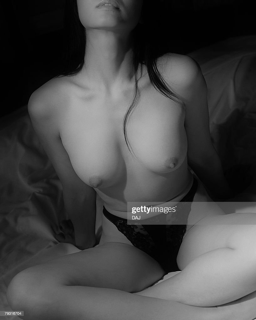 Woman in panties sitting on bed, black and white, front view : Stock Photo