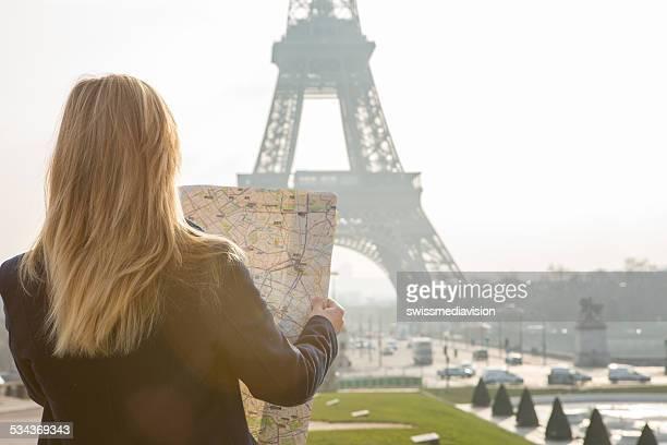 Frau in PAris-Eiffelturm-Blick in die Karte für die Anfahrt