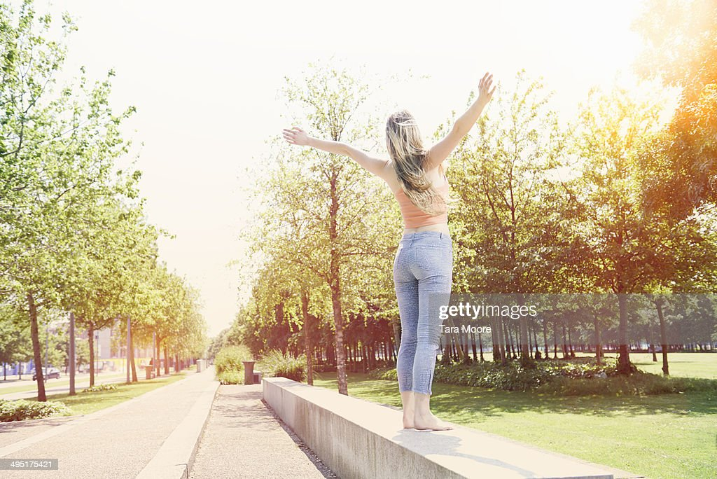 woman in park with arms outstretched : Stock Photo