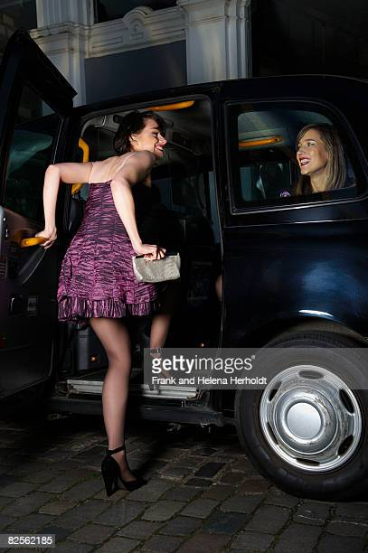 Woman in party dress entering taxi