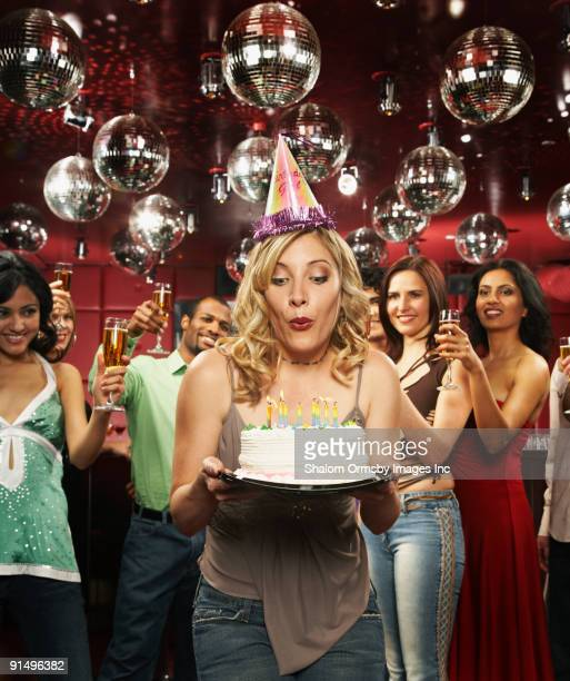 Woman in party hat blowing out candles on birthday cake