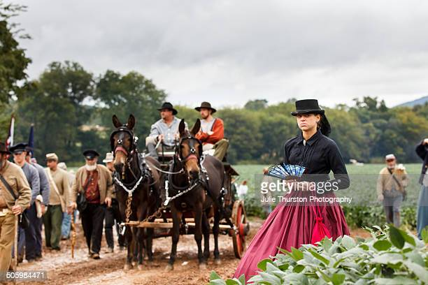 Woman in Period Costume Hat and Dress Watches Confederate Soldiers in Uniform and Horses and Wagon March in the Mud to the Battlefield During the...