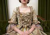 Woman in period dress sitting on couch, mid section