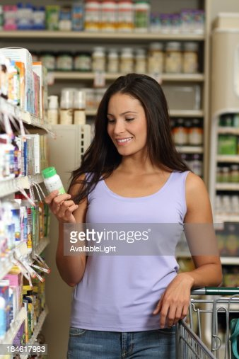Woman in Pharmacy Looks at Pills Vertical