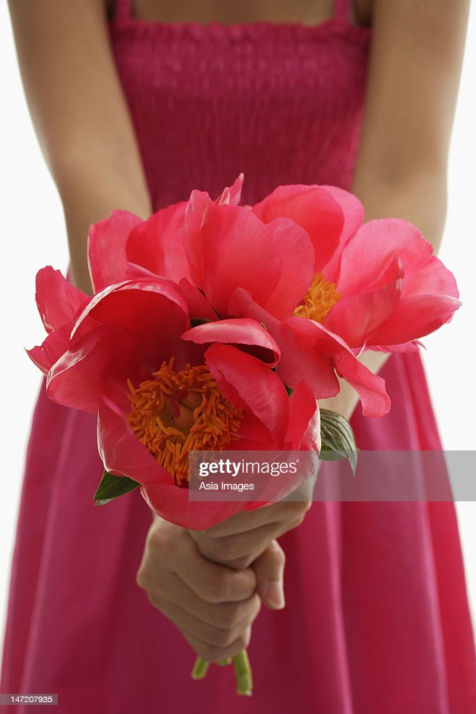 Woman in pink dress holding pink flowers. : Stock Photo