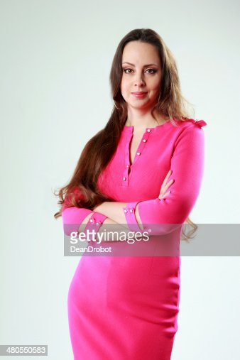 woman in pink dress with arms folded : Stock Photo