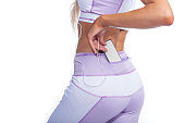 woman in pink sportswear with music player in pocket back view isolated